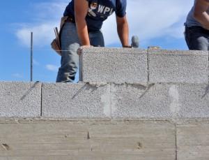 Artisan réalisant un mur en parpaing