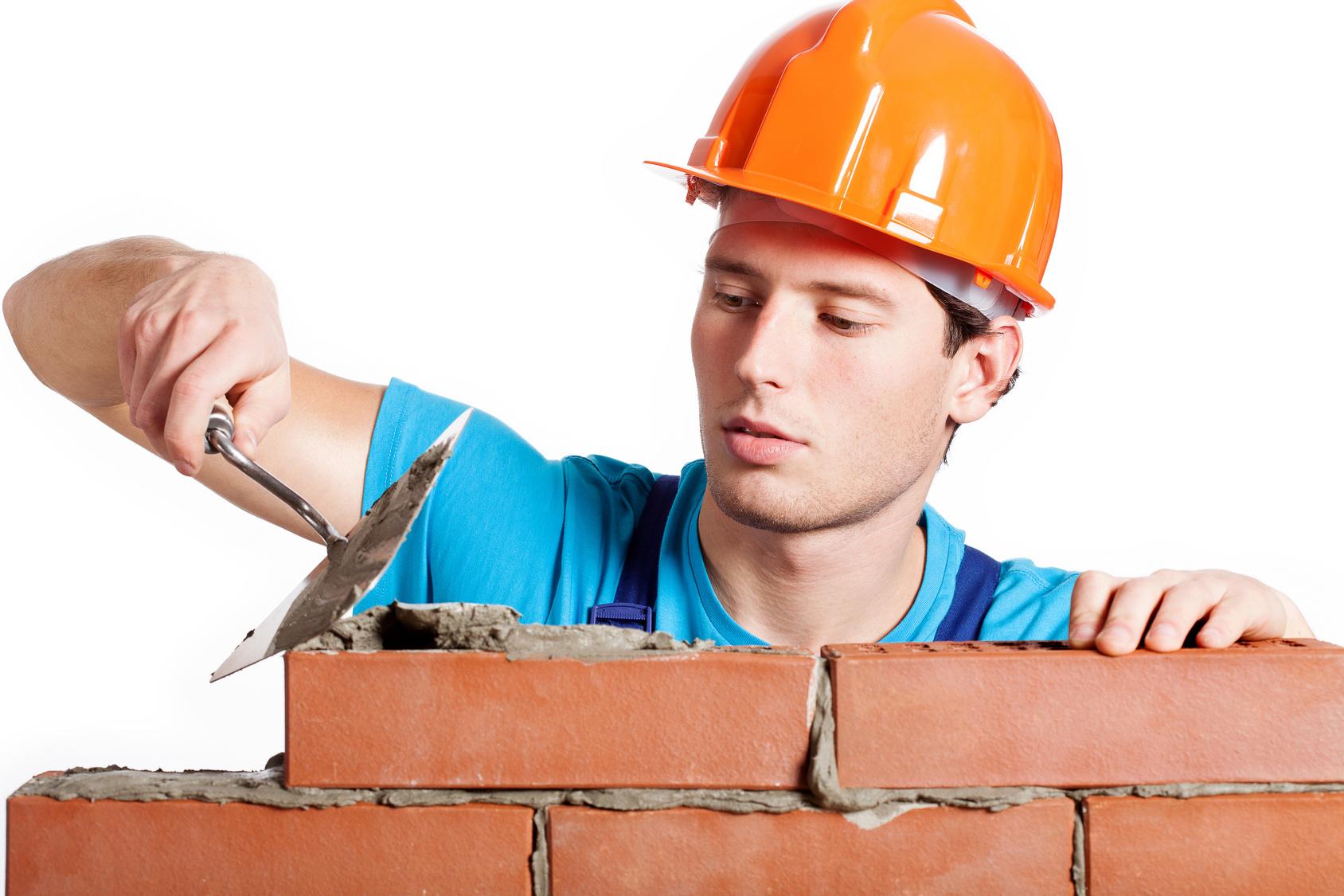 Artisan construisant mur briques.