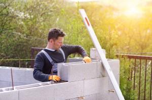 Artisan construisant mur béton.